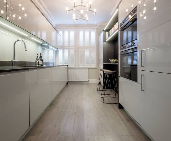 Monochromatic High Gloss Kitchen Design With New Contract Oak Look Laminate Floor Impervious To